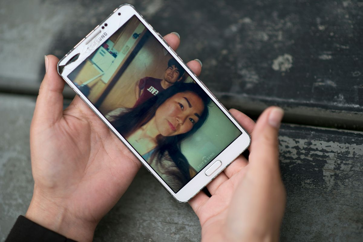 Yvonne Evan holds a photo on her phone of her daughter, Chynelle Lockwood.  (Marc Lester / Alaska Dispatch News)