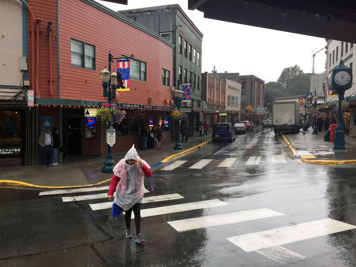 A tourist crosses South Franklin Street as a rain shower sends people scurrying for cover on Monday, August 14, 2017, in Juneau. (Erik Hill / ADN)