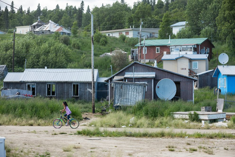 Syra Kozevnikoff, 9, rides her bicycle in Russian Mission in June. The tan building behind her is the village public safety office, which has three jail cells that are rarely used. (Loren Holmes / ADN)
