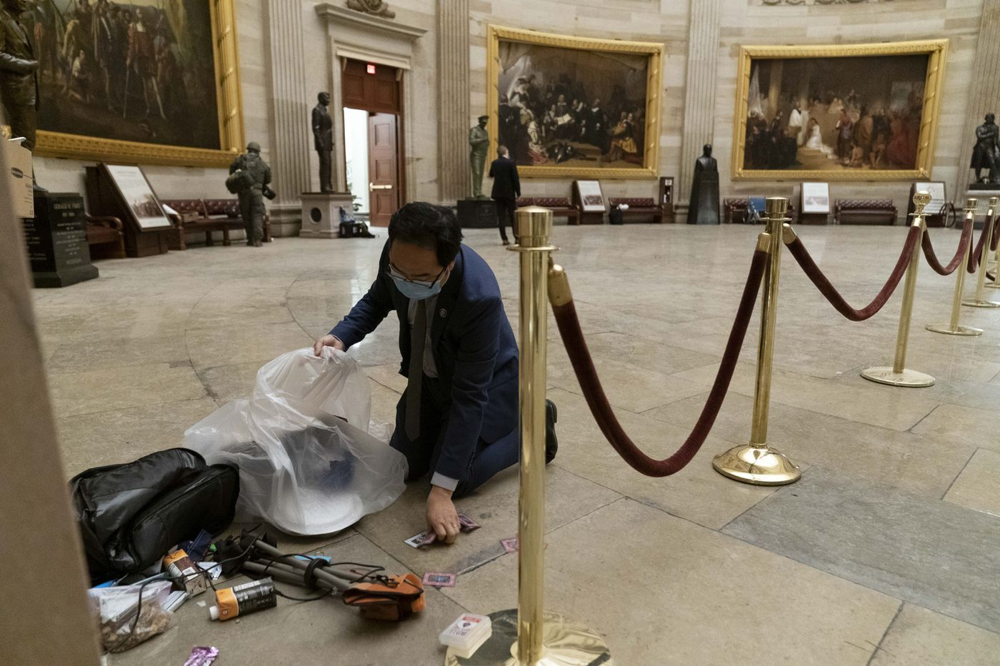 Rep. Andy Kim, D-N.J., cleans up debris and personal belongings strewn across the floor of the Rotunda in the early morning hours of Thursday, Jan. 7, 2021, after protesters stormed the Capitol in Washington, on Wednesday. (AP Photo/Andrew Harnik)