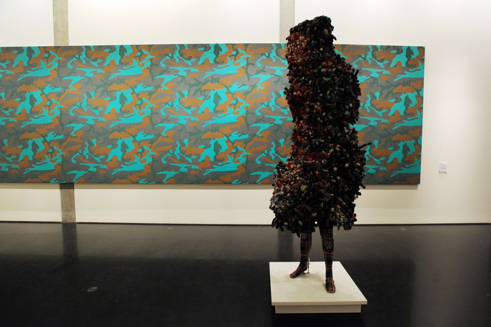 Soundsuit by Nick Cave stands near Camouflage by Andy Warhol. (Erik Hill / Alaska Dispatch News)