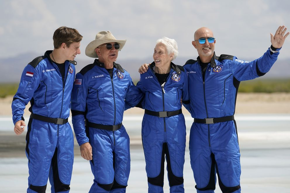 Oliver Daemen, from left, Jeff Bezos, founder of Amazon and space tourism company Blue Origin, Wally Funk and Bezos' brother Mark pose for photos in front of the Blue Origin New Shepard rocket, derby, after their launch from the spaceport near Van Horn, Texas, Tuesday, July 20, 2021. (AP Photo/Tony Gutierrez)