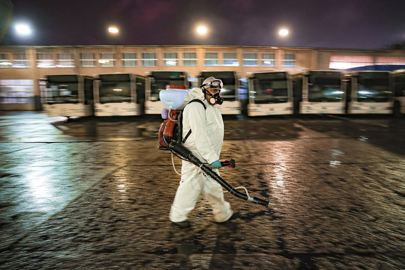 An employee of the pubic transport company wearing protective equipment walks during the daily disinfection of busses, part of the procedures to limit the spread of the coronavirus, in the early morning hours in Bucharest, Romania, Sunday, March 15, 2020. (AP Photo/Vadim Ghirda)