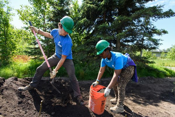 "Liam Lally, 17, fills a bucket for Denise Bamurange, 16. Six teens worked with leaders to help restore a bank of the Campbell Creek near Minnesota Drive on July 5, 2018. The crew is part of Youth Employment in Parks, a summer work program hosted by the Anchorage Park Foundation and Anchorage Parks and Recreation. The teens, ages 16-19, carried pails of soil, hammered holes in the ground to plant willows and spruce trees, and took plenty of water breaks as the worked on a warm day. The vegetation will bolster a bend in the creek that had been eroding toward the paved Campbell Creek Trail. It's just the latest project in the YEP's twelve-year history improving Anchorage Parks, said leader Annie DuBois. The ten-week summer program is designed to instill leadership skills in the conservation of public land. Sixteen-year-old Denise Baumrange said the work reminded her of work she did in Rwanda, where she moved to Anchorage from a few years ago. ""I like to work hard,"" Baumrange said. ""I feel like I'm earning something that I deserve."" (Marc Lester / ADN)"