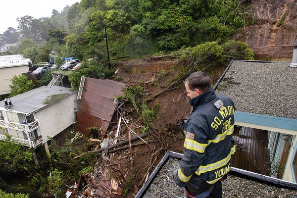 Firefighter/paramedic Patrick Young with the Southern Marin Fire Department looks out over the aftermath of a mudslide that destroyed three homes on a hillside in Sausalito, Calif., Thursday, Feb. 14, 2019. The National Weather Service says the atmospheric river sagged southward from Northern California overnight and is pointed at the southwestern corner of the state early Thursday. (AP Photo/Michael Short)