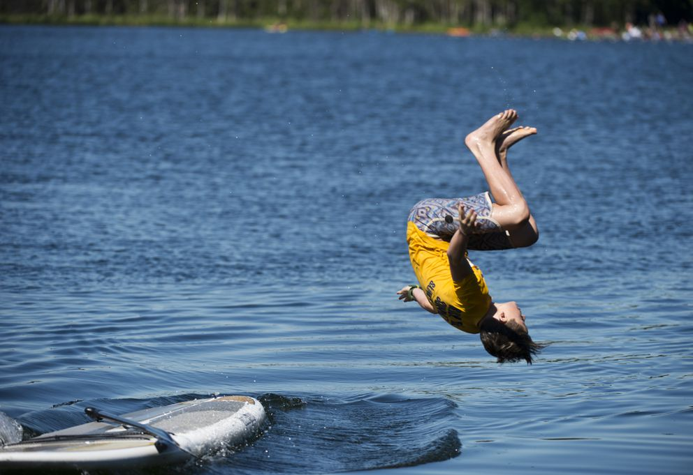 Zac Orr, 13, does a flip into Jewel Lake from a paddle board on July 2, 2018. Orr is visiting Anchorage from Honolulu, Hawaii. (Marc Lester / ADN)
