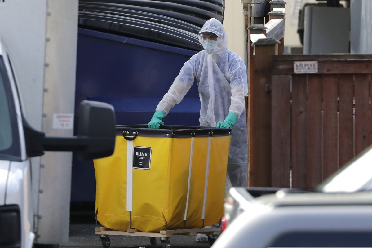 A member of a cleaning crew wheels a cart toward a vehicle at the Life Care Center, where at least 30 coronavirus deaths have been linked to the facility, Wednesday, March 18, 2020, in Kirkland, Wash. Staff members who worked while sick at multiple long-term care facilities contributed to the spread of COVID-19 among vulnerable elderly in the Seattle area, federal health officials said Wednesday. (AP Photo/Elaine Thompson)