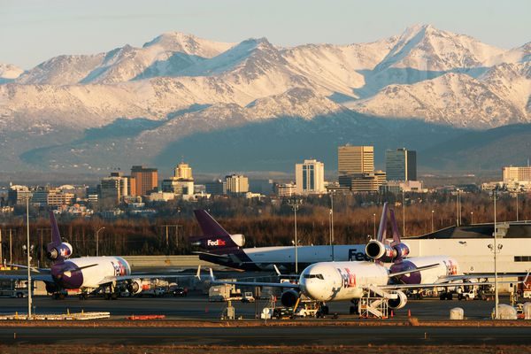 Afternoon sunshine breaks through clouds to bathe the Chugach Mountains, downtown Anchorage and Ted Stevens Anchorage International Airport in light on Wednesday, January 6, 2016, in a view from Point Woronzof Road.