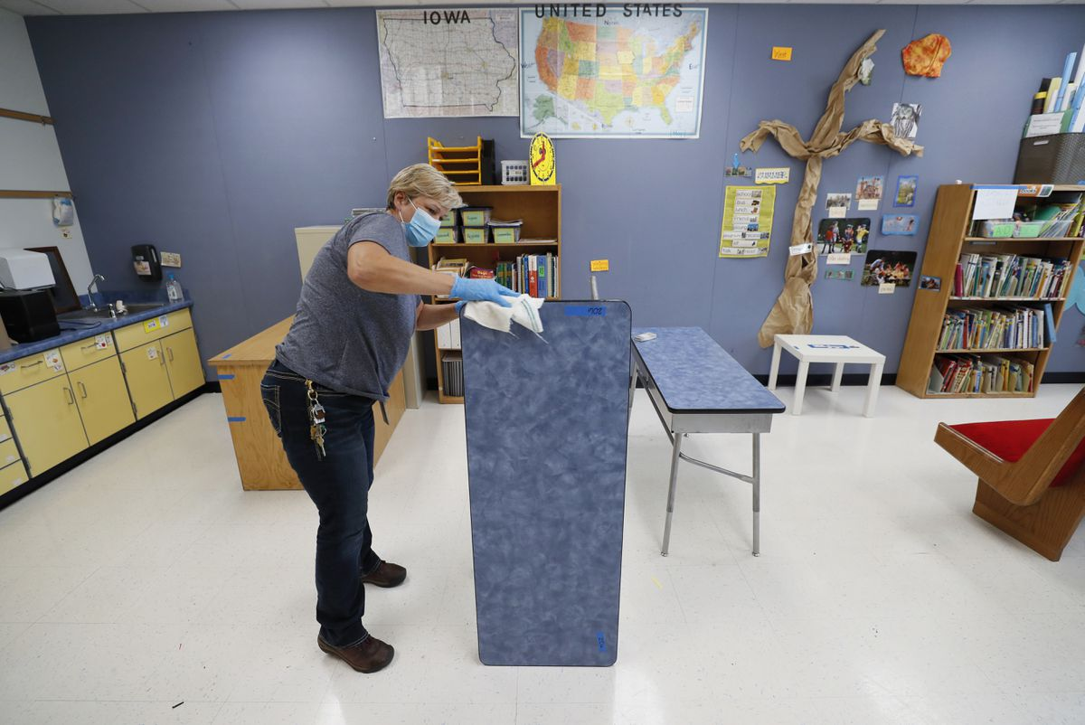 Des Moines Public Schools custodian Cynthia Adams cleans a desk in a classroom at Brubaker Elementary School, Wednesday, July 8, 2020, in Des Moines, Iowa. Getting children back to school safely could mean keeping high-risk spots like bars and gyms closed. That's the latest thinking from some public health experts. (AP Photo/Charlie Neibergall)