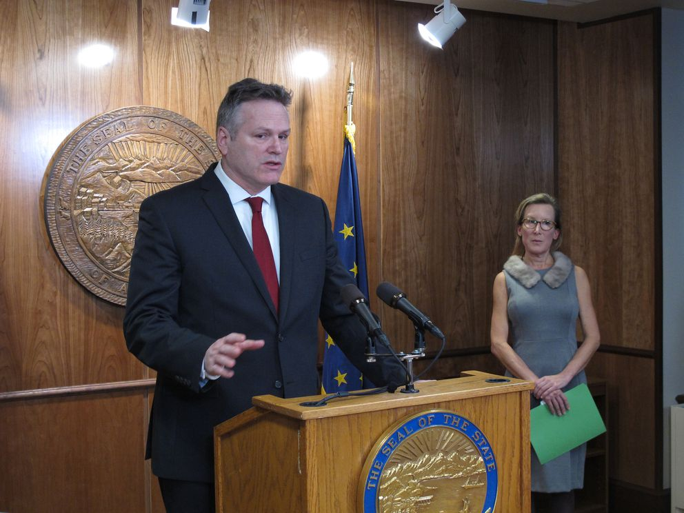 Alaska Gov. Mike Dunleavy speaks to reporters as his administration rolls out his budget plan in Juneau, Alaska, Wednesday, Feb. 13, 2019. The director of Dunleavy's budget office, Donna Arduin, is pictured on right. (AP Photo/Becky Bohrer)