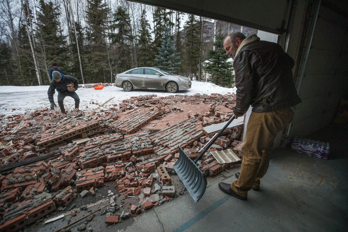 Josh Baker, left, helps his dad clean up brick siding in Eagle River on Saturday, Dec. 1, 2018. Steve Baker's home was badly damaged during a strong earthquake that shook southcentral Alaska on Friday. (Loren Holmes / ADN)