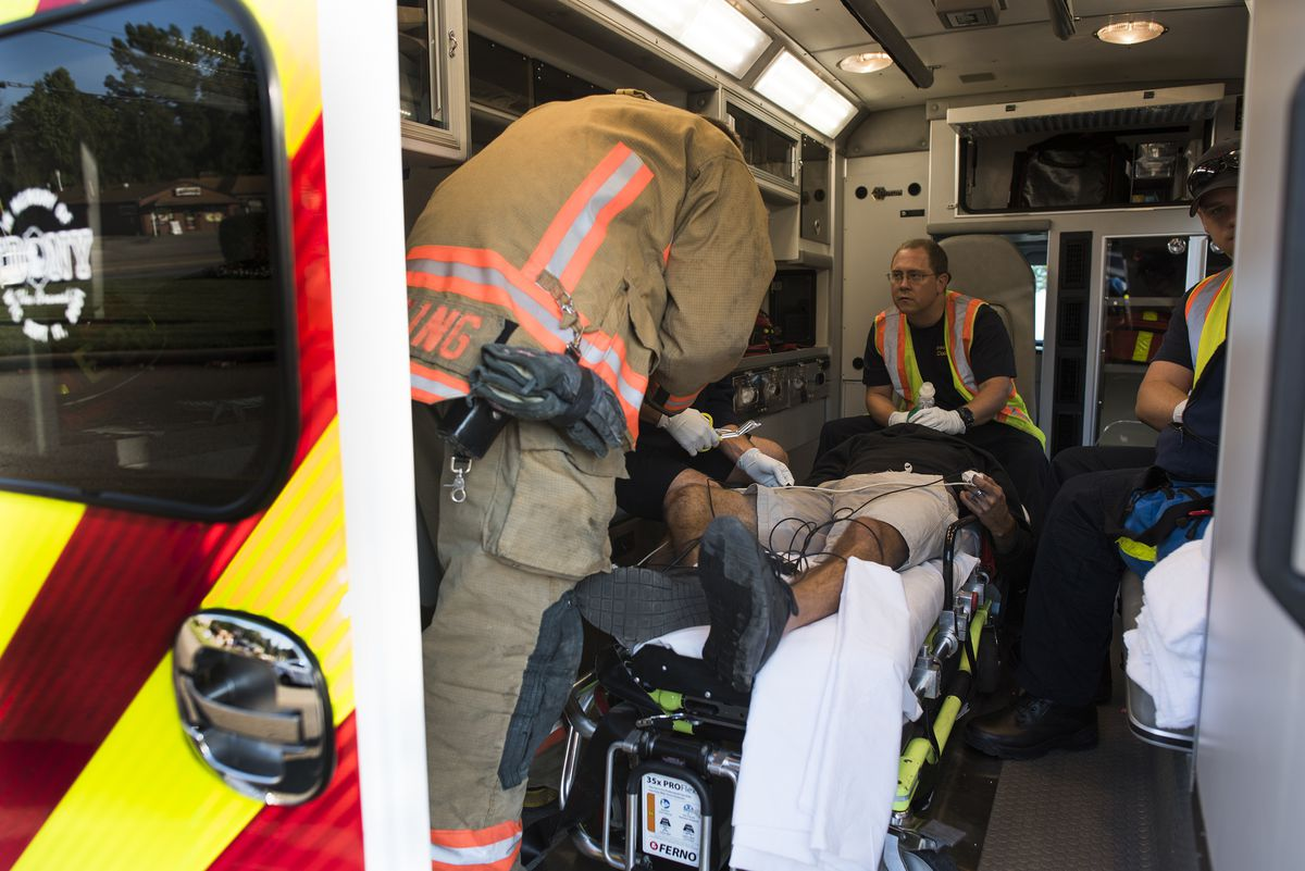 Medics from the Colerain Township Fire Dept. resuscitate a victim of an auto accident who overdosed on heroin, in Colerain Township, Ohio, on Friday. (Ty Wright / The New York Times)