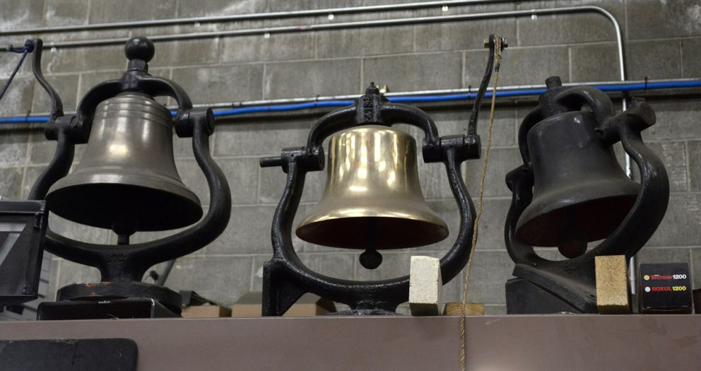 Bells sit atop an office at the Engine 557 restoration site on Wednesday. The original engine bell at right was made of cast iron, as brass was in demand when the engine was manufactured during World War II. The sweet-sounding bell brass model at left was placed on the engine in Washington state. A Panama Canal-era brass bell at center arrived in Alaska with railroad equipment following completion of that project. (Erik Hill / Alaska Dispatch News)