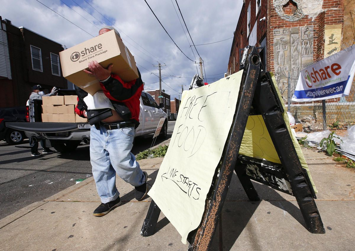 A resident carries his box of food from the Share Food Program distributed at the Young Chances Foundation in the Point Breeze neighborhood of Philadelphia last spring. President Joe Biden's $6 trillion budget request proposes record spending to reduce historical disparities in underserved communities. (Yong Kim/Philadelphia Inquirer/TNS)