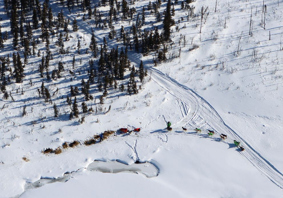 Ryan Redington with his team in harness (right) stops near a team bedded down near the trail as the race heads toward the checkpoint of Rohn on Saturday. (Zachariah Hughes/for ADN)