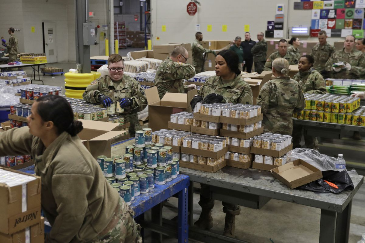 FILE - In this March 24, 2020, file photo, members of The Ohio National Guard assist in repackaging emergency food boxes for food distribution at the Cleveland Food Bank in Cleveland. (AP Photo/Tony Dejak, File)