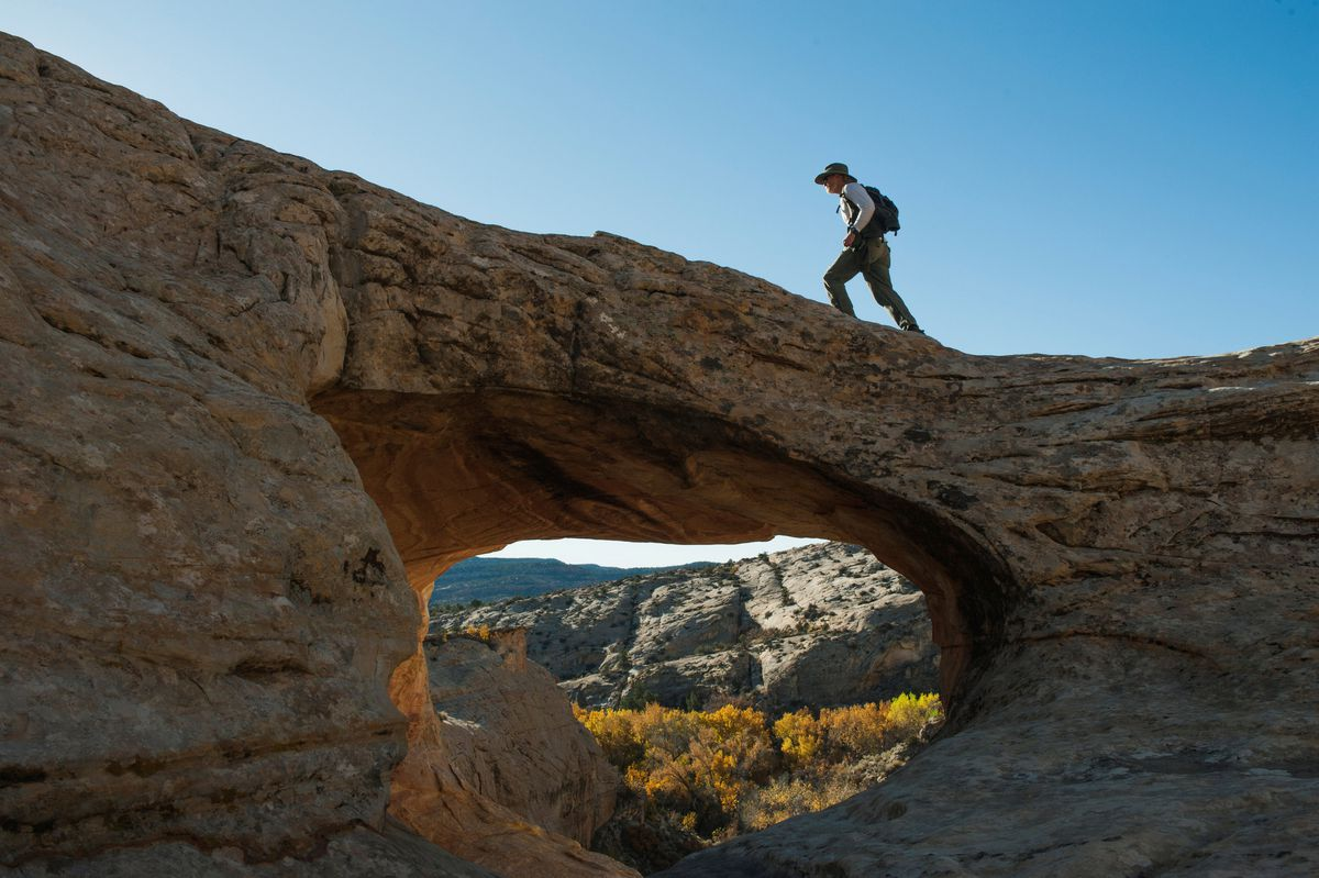 A hiker crosses a natural bridge at Butler Wash in Bears Ears National Monument near Blanding, Utah. REUTERS/Andrew Cullen/File