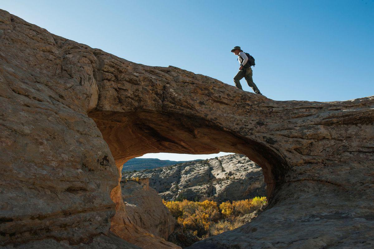 A hiker crossesa natural bridge at Butler Wash in Bears Ears National Monument near Blanding, Utah. REUTERS/Andrew Cullen/File