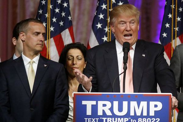 In this March 15, 2016 file photo, Donald Trump's campaign manager Corey Lewandowski listens at left are Trump speaks in Palm Beach, Fla. Florida police have charged Lewandowski with simple battery in connection with an incident earlier in the month involving a reporter.