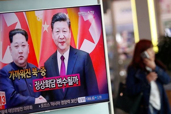 A woman walks past a TV broadcasting a news report on a meeting between North Korean leader Kim Jong Un and Chinese President Xi Jinping in Beijing, in Seoul, South Korea, March 28, 2018. REUTERS/Kim Hong-Ji