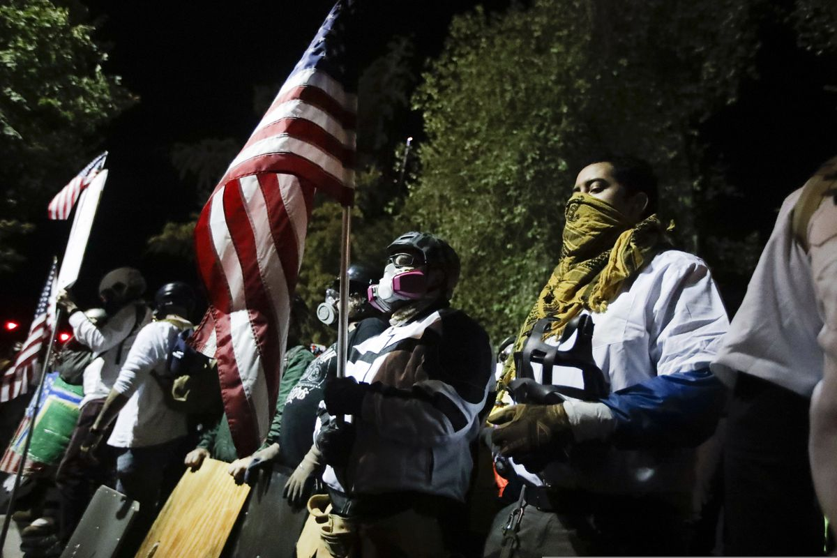 Military veterans participate in a Black Lives Matter protest at the Mark O. Hatfield United States Courthouse Thursday, July 30, 2020, in Portland, Ore. After days of clashes with federal police, the crowd outside of the federal courthouse remained peaceful Thursday night. (AP Photo/Marcio Jose Sanchez)