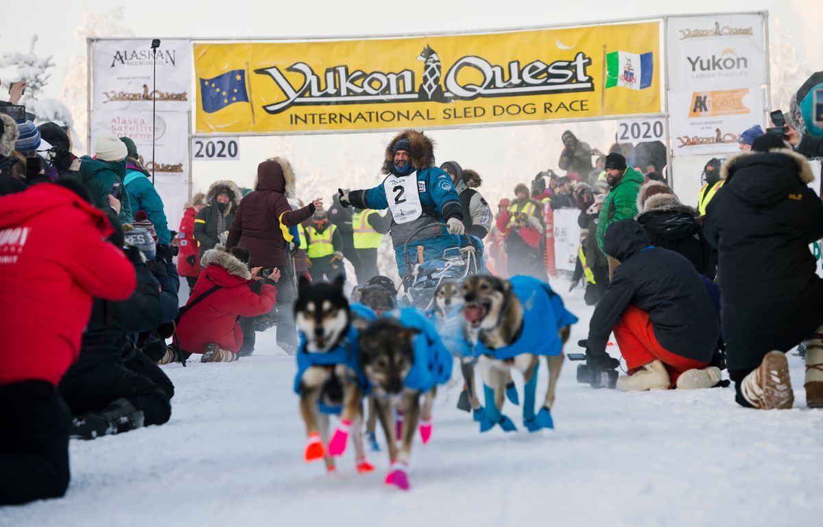 Cody Strathe of Cantwell gives a high five as he leaves the starting line of the Yukon Quest International Sled Dog Race in Fairbanks on February 1, 2020. (Marc Lester / ADN)