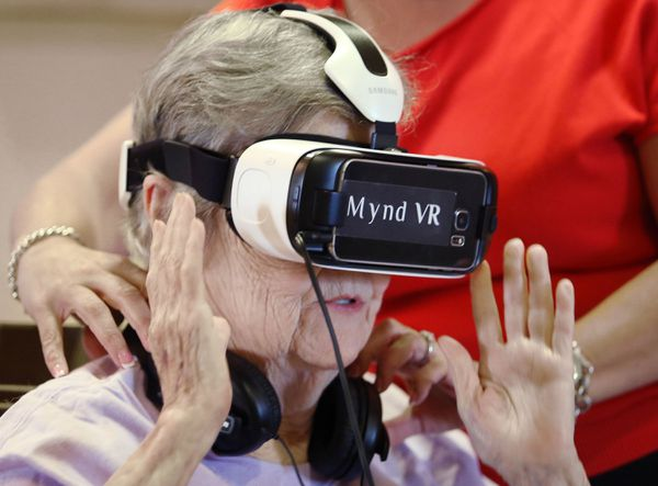 Jane Auchter, 85, a resident at Encore at Avalon Park assisted living facility, takes a virtual-reality trip to the Grand Canyon on July 12, 2017. (Stephen M. Dowell/Orlando Sentinel/TNS)
