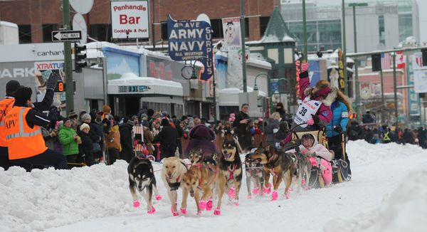 DeeDee Jonrowe waves to people in the parking garage during the 2018 Iditarod Trail Sled Dog Race ceremonial start in downtown Anchorage on Saturday. (Bob Hallinen / ADN)