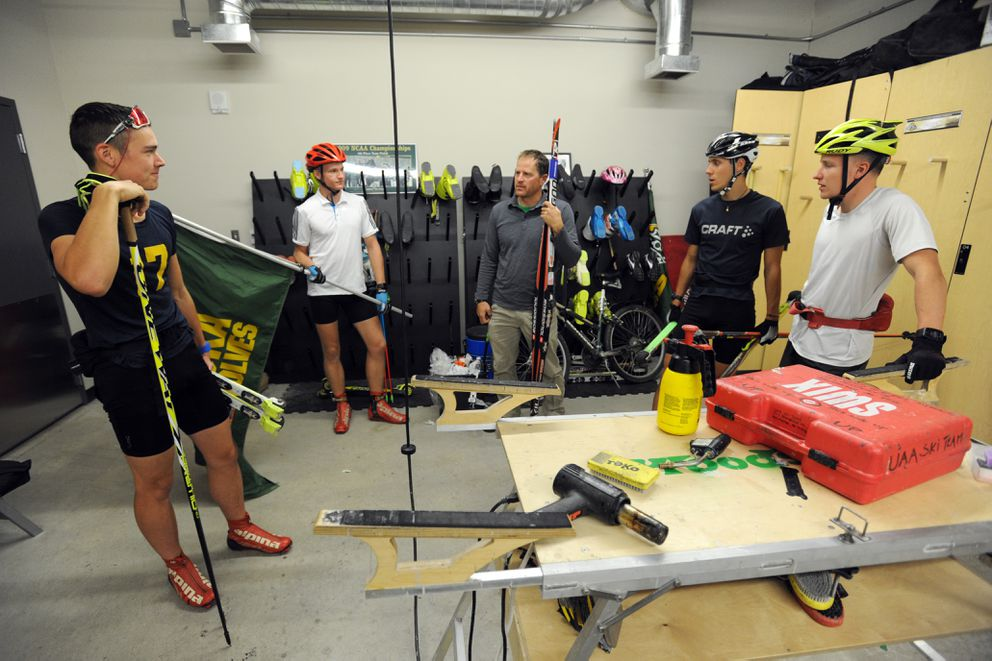 UAAski coach Andrew Kastning, center, confers with Aslak Eira, left, Zackarias Toresson, center left, Pietro Mosconi, center right, and Toomas Kollo in the ski equipment room before heading outside for roller-ski training. (Erik Hill / Alaska Dispatch News)