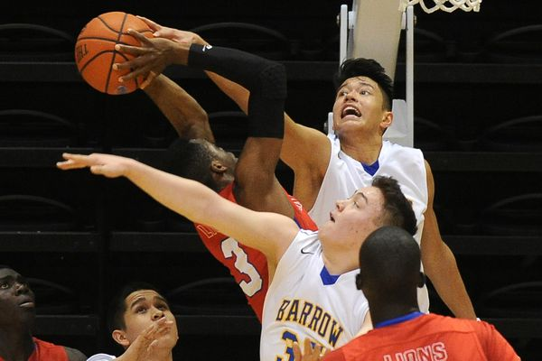 Kamaka Hepa (top) blocks a shot for Barrow in a game against Anchorage Christian at the 2016 Class 3A state basketball tournament. (Bob Hallinen / ADN archive 2016)