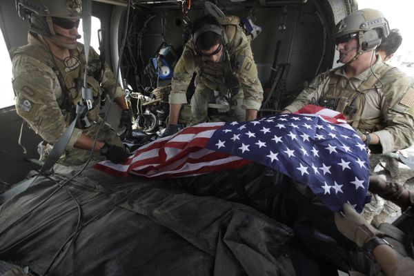 Upon landing after a helicopter rescue mission, Tech. Sgt. Jeff Hedglin, right, an Air Force Pararescueman, or PJ, drapes an American flag over the remains of the first of two U.S. soldiers killed minutes earlier in an IED attack, assisted by fellow PJs, Senior Airman Robert Dieguez, center, and 1st Lt. Matthew Carlisle, in Kandahar province, southern Afghanistan on July 29, 2010. (AP Photo/Brennan Linsley, File)
