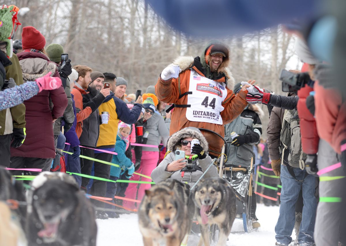 Brent Sass mushes through a trailgate party Saturday during the Iditarod ceremonial start. (Anne Raup / ADN)