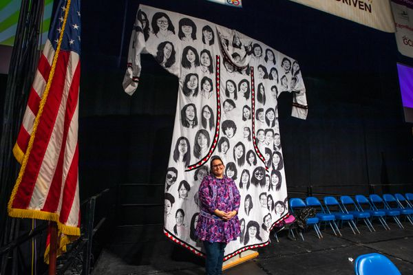 Amber Webb stands with her 12-foot qaspeq Thursday, Oct. 17, 2019 during the Alaska Federation of Natives convention at the Carlson Center in Fairbanks. Webb made the qaspeq, which displays portraits of over 200 Alaskan, Canadian, and Native American Murdered Indigenous Women and Girls. Webb received the 2019 Dr. Walter Soboleff