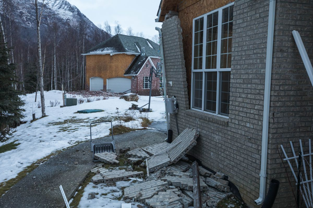 Brick siding lies on the ground in an Eagle River neighborhood Saturday morning. The homes were badly damaged during a strong earthquake that shook Southcentral Alaska on Friday. (Loren Holmes / ADN)
