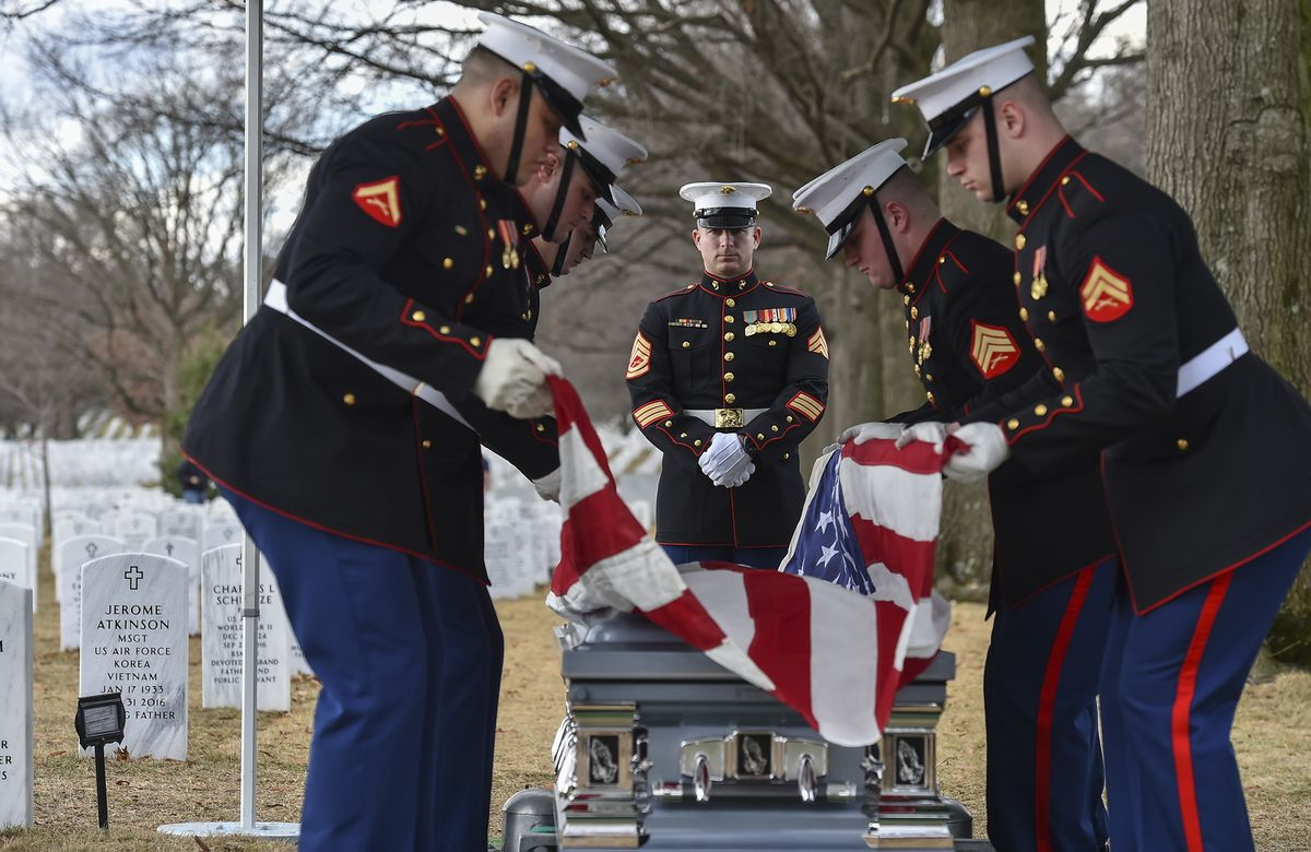 Members of the Marine Corps Body Bearers raise the American flag Tuesday from the casket of retired Marine Master Sgt. Catherine G. Murray at Arlington National Cemetery. (Washington Post photo by Ricky Carioti)