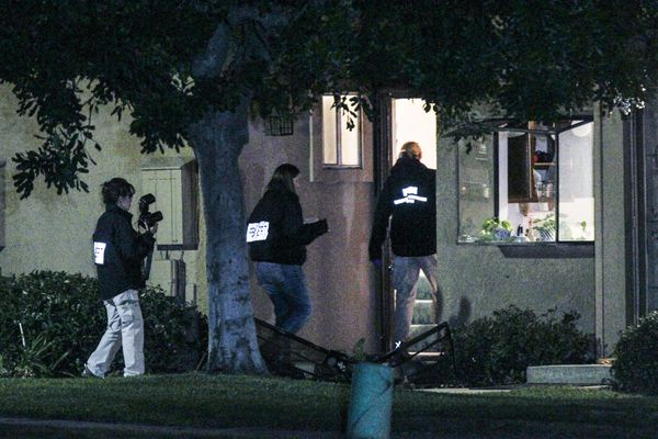 FBI agents search outside a home Thursday in connection to the shootings in San Bernardino.