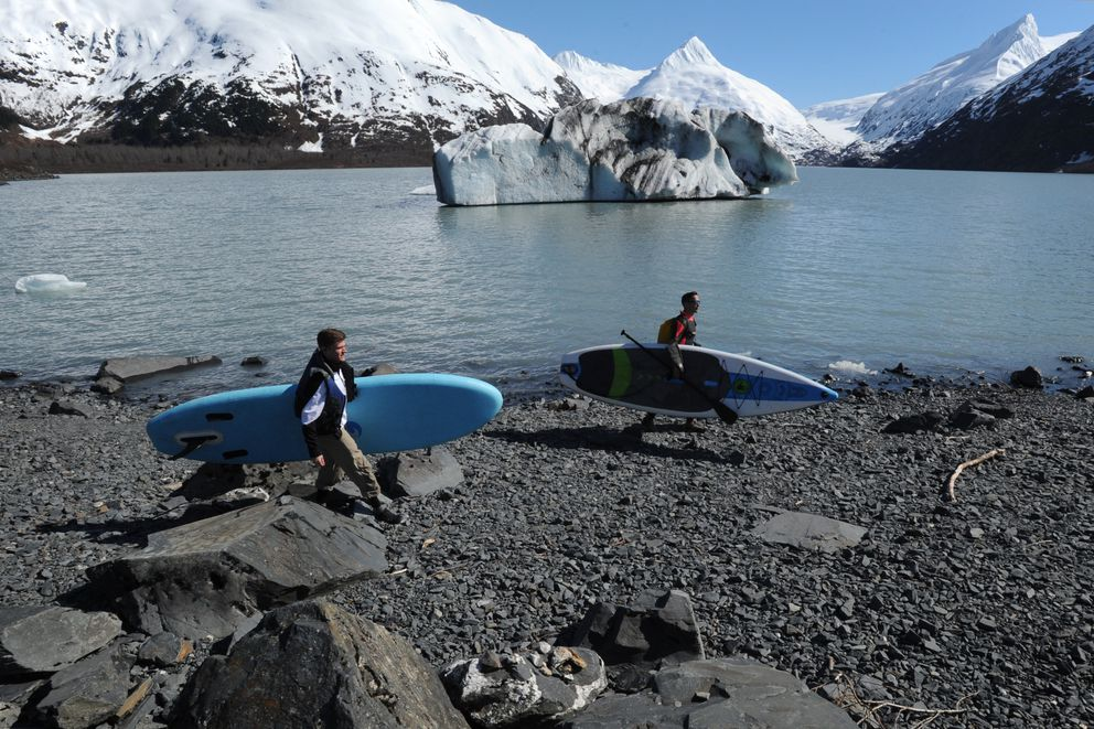Jon Rippe and John Limon carry paddleboards to the parking lot on Sunday, April 14, 2019, after they paddled across Portage Lake to Portage Glacier, where they witnessed the glacier calving. (Bill Roth / ADN)