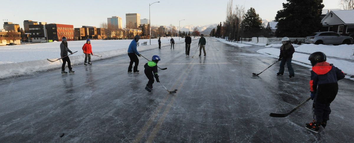 Skaters took to the icy streets near downtown Anchorage and played hockey on 10th Avenue along Delaney Park Strip on Sunday, Dec. 8, 2019. (Bill Roth / ADN)