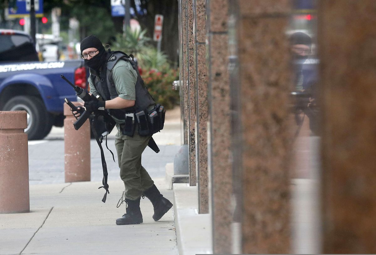 An armed shooter stands near the Earle Cabell Federal Building Monday, June 17, 2019, in downtown Dallas. The shooter was hit and injured in an exchange of gunfire with federal officers outside the courthouse. (Tom Fox/The Dallas Morning News)