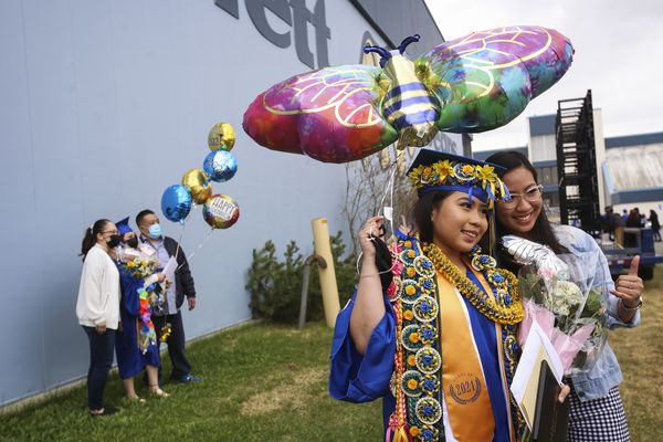 Friends and family take photographs with graduating seniors after the Bartlett High School graduation ceremony in Anchorage on Monday, May 10, 2021. There are about 3,000 graduating seniors districtwide for the Anchorage School District. (Emily Mesner / ADN)