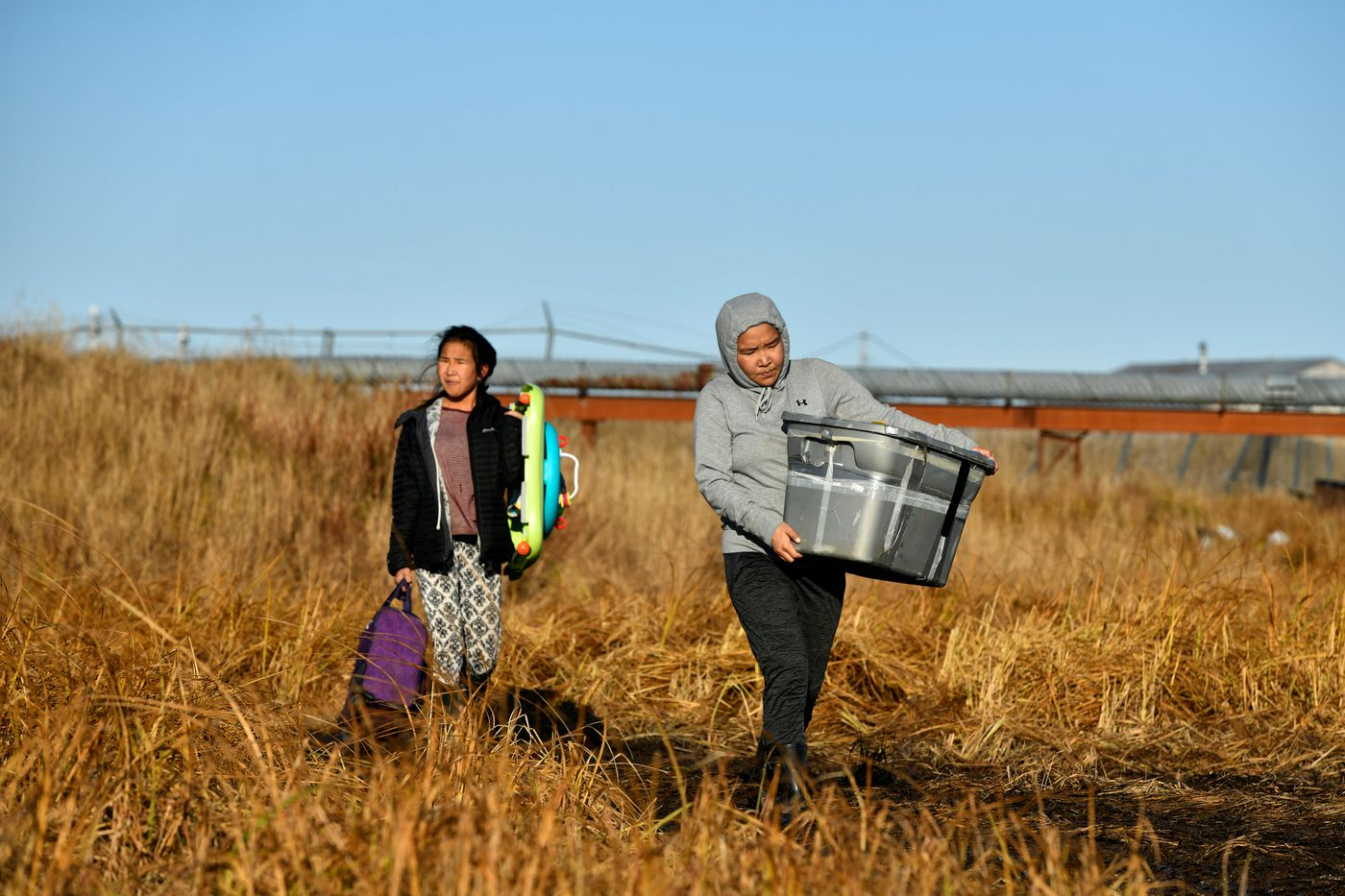 Gwendolyn David, 14, left, and Joann David, 15, carry belongings toward boats in Newtok. (Marc Lester / ADN)