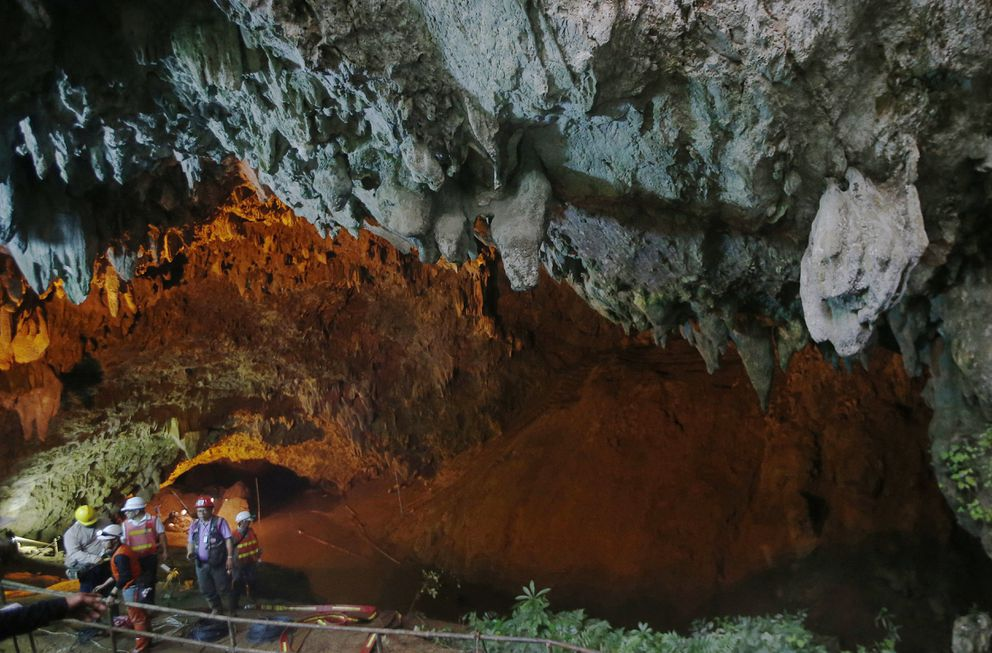 FILE - In this Thursday, June 28, 2018, file photo, rescue personnel walk out of the entrance to a cave complex where it's believed that 12 youth soccer team members and their coach went missing, in Mae Sai, Chiang Rai province, in northern Thailand. For the boys and their coach, we have only a hint of what it might have been like. But for the rest of us, watching from afar as the world's journalists beamed us live shots and the unknowable became known drip by captivating drip, we knew only one thing: It was hard to look away. (AP Photo/Sakchai Lalit, File)