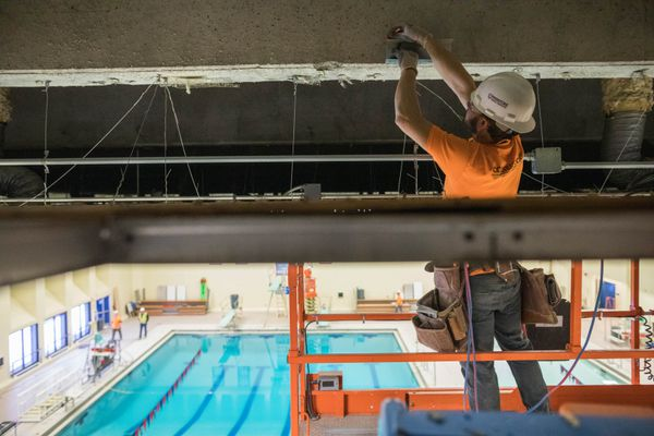 Daniel Unfreid, with Cornerstone General Contractors, works on a seismic repair and upgrade to the East High pool ceiling on Friday, Jan. 4, 2019. The school was damaged during the Nov. 30 earthquake. (Loren Holmes / ADN)