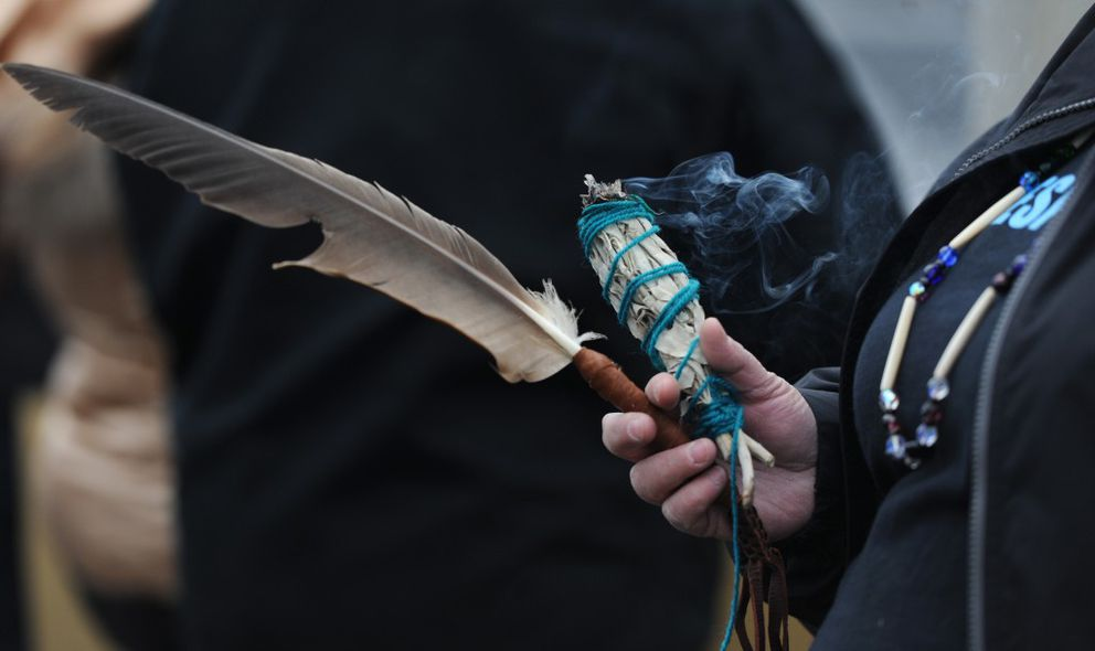 Lisa Wade holds sage and a feather used for smudging as Alaskans gathered to show their support for the Standing Rock Sioux Tribe and their battle against the Dakota Access Pipeline on Sunday. (Bill Roth / Alaska Dispatch News)