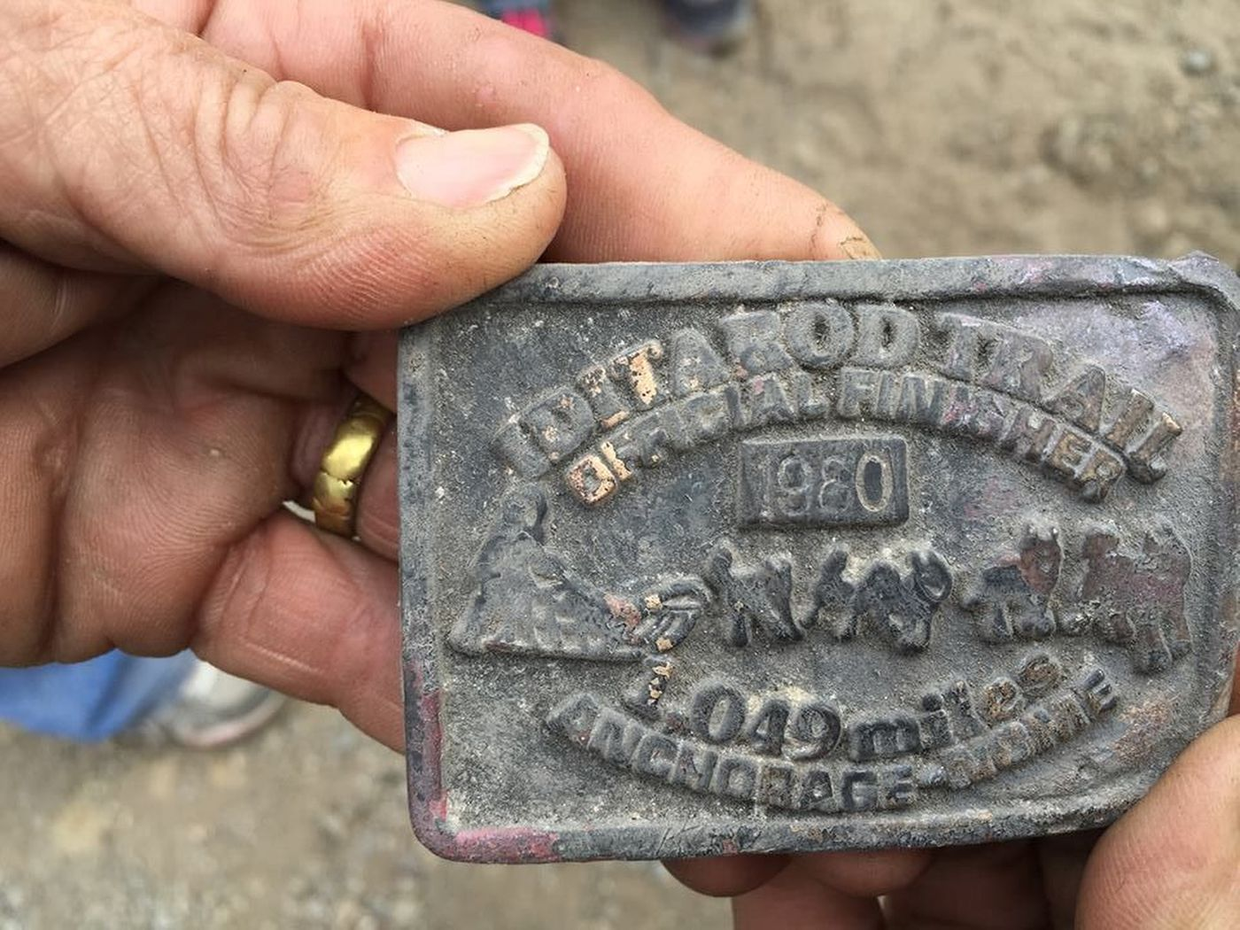 DeeDee Jonrowe holds the belt buckle she received after her first Iditarod after it was recovered in the fire wreckage.