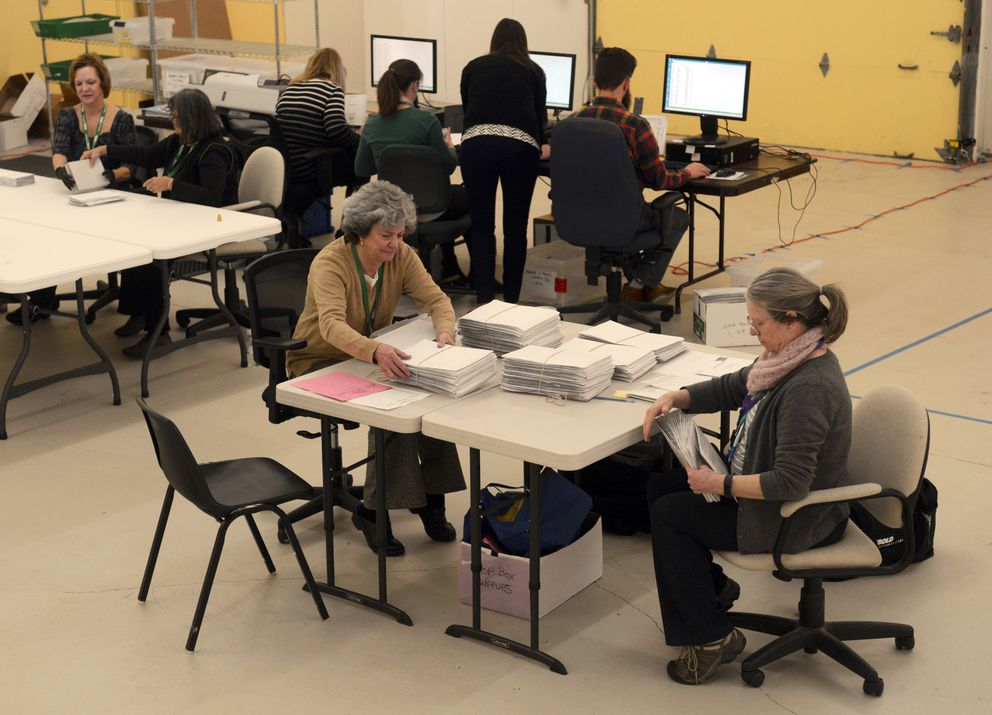 """Lo Hansen, foreground left, and Cindy Hawkins, foreground right, prepare absentee and early voting ballots from the Loussac Library polling station for counting on Tuesday as the review team works at the new municipal election center at Ship Creek on Monday. """"This is our first election here,"""" said Amanda Moser, deputy municipal clerk for elections. """"It's fantastic all being in the same room."""" Elections staffers used to be scattered throughout City Hall. """"I wore a Fitbit last year and I would get 100 flights of stairs running back and forth,"""" she said. (Erik Hill / Alaska Dispatch News)"""