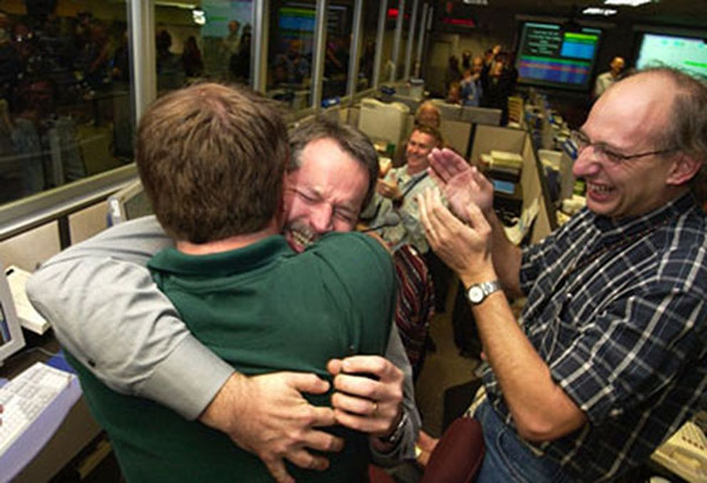 Entry, descent and landing manager Rob Manning, facing the camera, hugs Richard Cook, the current Mars Exploration Rover project manager after Opportunity's successful landing on Mars. To their right, Miguel San Martin, a member of the attitude control systems team, cheers the victory. Handout courtesy of NASA/JPL-Caltech