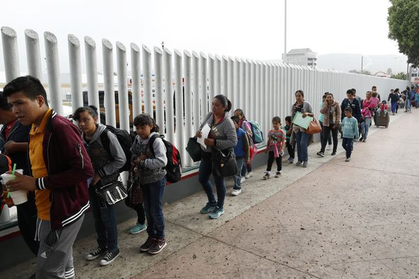 FILE - In this Thursday, July 26, 2018 photo people line up to cross into the United States to begin the process of applying for asylum near the San Ysidro port of entry in Tijuana, Mexico. A federal judge has extended a freeze on deporting families separated at the U.S.-Mexico border, giving a reprieve to hundreds of children and their parents to remain in the United States. U.S. District Judge Dana Sabraw said in his order Thursday, Aug. 16, 2018, that