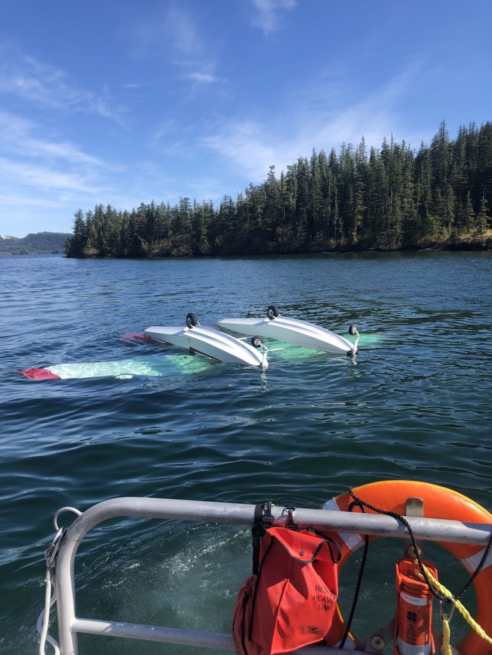 A Cessna A185F Skywagon is upside down in Cascade Bay, 20 miles southwest of Valdez, Alaska, May 21, 2019. Coast Guard Station Valdez small boat crews, an Alaska Air National Guard rescue helicopter crew and four good Samaritans responded to a report of a downed aircraft with three people aboard. One passenger died in the crash. (U.S. Coast Guard photo)