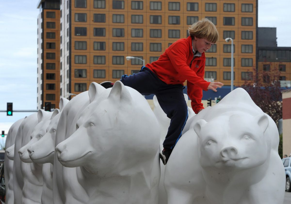 Henry Wirch, 9, of Boston, climbs down after sitting on one of the full-size, fiberglass bear statues parked outside the Westmark Anchorage Hotel on Sunday, June 26, 2016. (Bill Roth / Alaska Dispatch News)